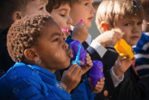 Pre-K students blow bubbles at the dedication of Noah's Garden